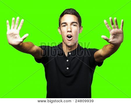 portrait of young man doing stop symbol against a removable chroma key background