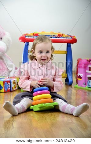 Little Girl In A Room With Toys, Playing With Color Pyramid