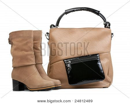 Pair of female boots and handbag over white