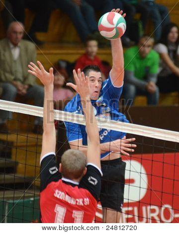 KAPOSVAR, HUNGARY - OCTOBER 29: Karoly Lesznyik (in blue) in action at a Hungarian National Championship volleyball game Kaposvar (blue) vs. Szolnok (red), October 29, 2011 in Kaposvar, Hungary.