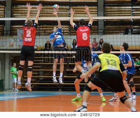 KAPOSVAR, HUNGARY - OCTOBER 29: Karoly Lesznyik (2nd from L) in action at a Hungarian National Championship volleyball game Kaposvar (blue) vs. Szolnok (red), October 29, 2011 in Kaposvar, Hungary.