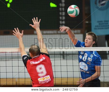 KAPOSVAR, HUNGARY - OCTOBER 29: Roland Gergye (R) in action at a Hungarian National Championship volleyball game Kaposvar (blue) vs. Szolnok (red), October 29, 2011 in Kaposvar, Hungary.