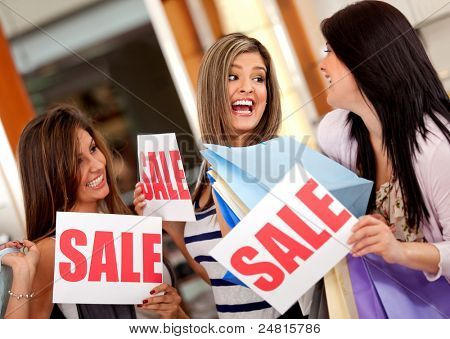 Excited group of women with bags shopping on sale