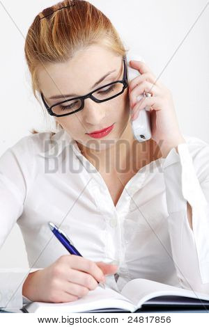 Answering the telephone pretty caucasian woman writing in the office.