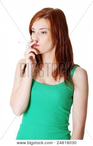Pretty standing teen caucasian smoking girl. Isolated on white background.