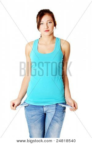 Young caucasian teenage girl standing and showing her empty pockets. Isolated on white.