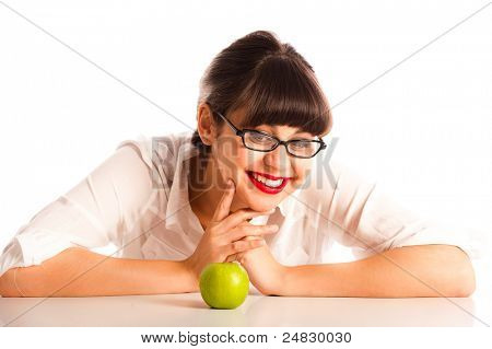 Professional young woman resting on a desk with an apple and glasses. Smiling at the apple