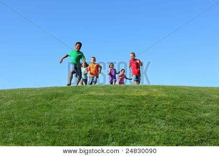 Group of kids running on grass hill with blue sky