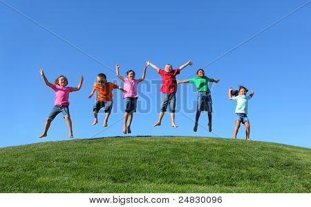 Group of  kids jumping on grass hill with blue sky