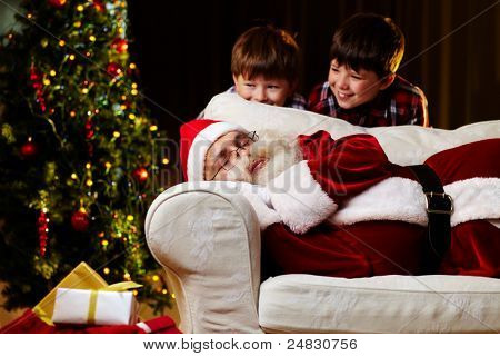 Photo of Santa Claus sleeping on sofa with two happy boys looking at him