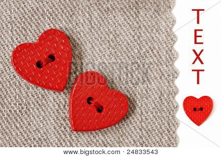 Extreme closeup of tiny heart shaped buttons sewn on natural cotton fabric with white background and copy space.