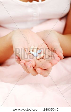 Close up on beautiful caucasian woman hands in bed holding pills.