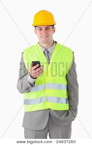 Portrait of a young builder holding his cellphone against a white background