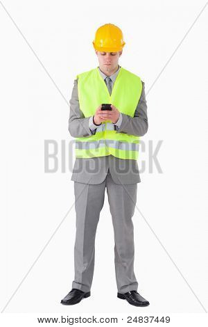 Portrait of a young builder using his cellphone against a white background