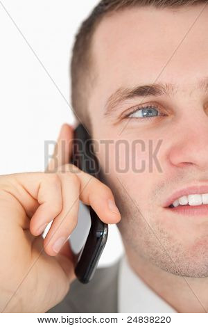Close up of a handsome businessman making a phone call against a white background