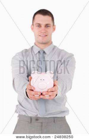 Portrait of a young businessman holding a piggy bank with the camera focus on the object