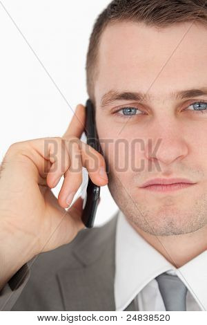 Close up of a serious businessman making a phone call against a white background