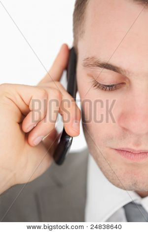 Close up of a sad businessman making a phone call against a white background