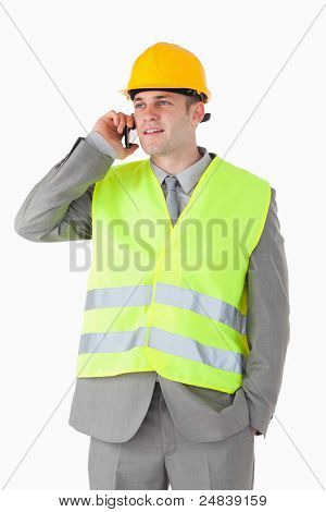 Portrait of a handsome builder using his cellphone against a white background