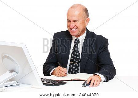 hombre de negocios senior de Smiley sentados en el lugar de trabajo y escribiendo en la agenda
