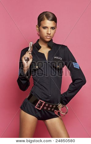 Attractive young woman wearing a sexy police costume holding a gun