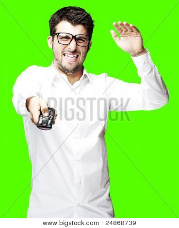 portrait of angry man changing channel using a remote tv control over removable chroma key background