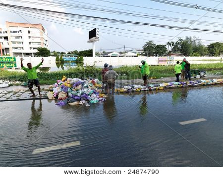 PHATHUMTRANI, THAILAND- OCTOBER 21: Volunteers rescue workers and army build sand bag walls, during the worst flooding disaster   on October 21, 2011 Rongsit Road, Phathumtrani, Thailand.