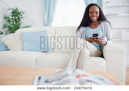Smiling woman writing text message while sitting on couch