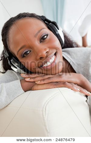 Close up of smiling woman enjoying music on her sofa