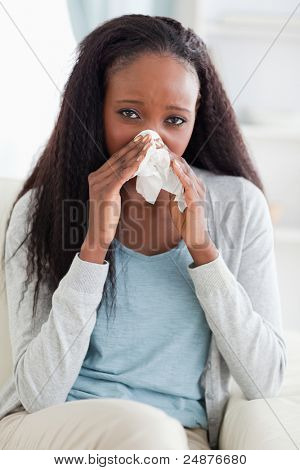 Close up of young woman on couch blowing her nose