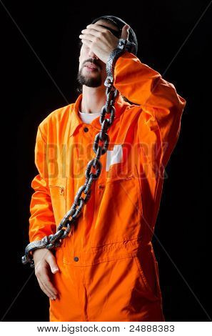 Inmate chained on black background