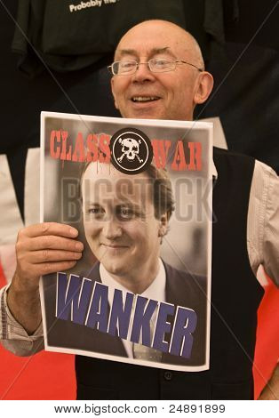 Class War activist holds up a poster about British Prime Minister David Cameron