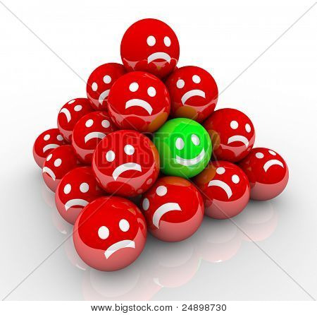 One happy face in a pyramid of balls with sad, unhappy faces symbolizing a unique person in a good mood surrounded by grumpy, dissatisfied others