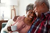 Loving Senior Couple Sitting On Sofa At Home Relaxing With Hot Drink poster