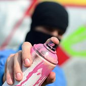 A Young Graffiti Artist In A Blue Jacket And Black Mask Is Holding A Can Of Paint In Front Of Him Ag poster