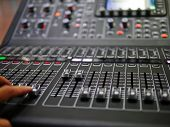 Soft Focus Hand Adjusting Professional Digital Audio Mixer Controller In The Control Room, Sound Mix poster