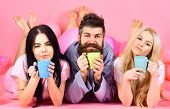 Man And Women, Friends On Sleepy Faces Lay, Pink Background. Lovers Drinking Coffee In Bed. Threesom poster