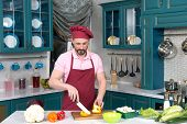 Serious Cook In Red Apron And Red Bonnet At Kitchen Cut Yellow Paprika For Two Parts On Cutting Boar poster