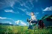 An Asian Woman Is Sitting On The Camping Chair In Front Of The Tent With Red Backpack. She Is Drinki poster
