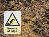 Warning Sign At The Edge Of An Unstable Cliff Edge poster