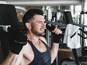 Stylish, Muscular Man In Black Training Gloves And Short Sports Shirt, Performs Strength Exercises O poster