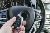 Mans Hand Holding A Wireless  Car Key In Black Leather Interior. Modern Car Interior Details. Car D poster