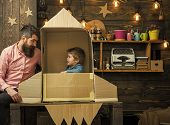 Home Airfield. Boy Play With Dad, Father, Little Cosmonaut Sit In Rocket Made Out Of Cardboard Box.  poster