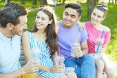 Affectionate and happy teens having drinks and talking outdoors on summer day poster