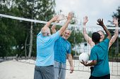 Smiling Multiethnic Old Volleyball Players Giving High Five To Each Other After Game poster