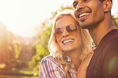Beautiful young couple hugging and looking away outdoors at sunset. Portrait of happy boyfriend embr poster