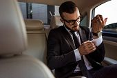 View Of Handsome Businessman Buttoning Cuff In Car poster