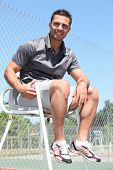 picture of umpire  - Smiling friendly tennis umpire sitting in the sunshine - JPG