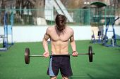 One More Time. Man Athlete Training Outdoor With Barbell. Athletic Man Lifts Up Heavy Barbell. Athle poster