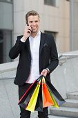 Businessman Shopping. Man Carries Shopping Bags While Have Phone Conversation Urban Background. Succ poster
